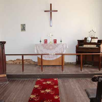Chapel with organ and central table. there is a skull on the organ